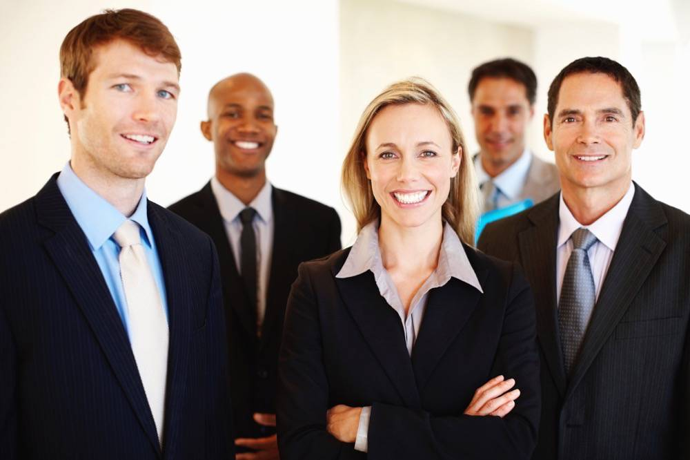 Portrait of elegant female executive smiling with multi racial team